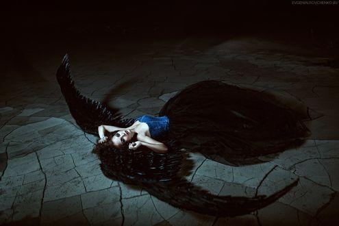 Фото Грустная девушка ангел с огромными черными крыльями лежит на потрескавшейся земле. Фотограф Евгения Литовченко / Evgeniya Litovchenko