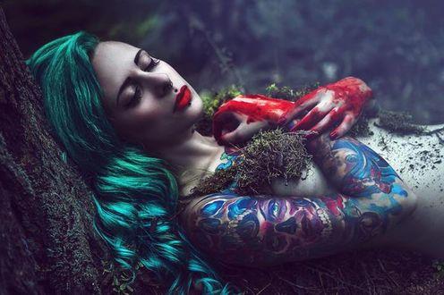 Фото Полуобнаженная девушка с закрытыми глазами с зелеными волосами с татуировками, прикрыв грудь окровавленными руками осыпанная мхом лежит у дерева, by Karolina Ryvolova