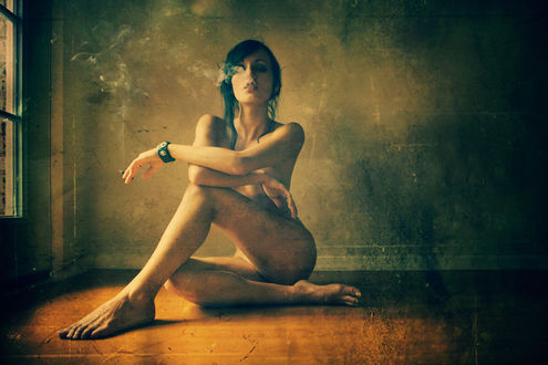 Фото Обнаженная девушка сидит на полу с сигаретой в руке