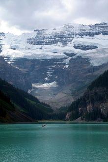 Фото Люди плывут на лодке в горном озере