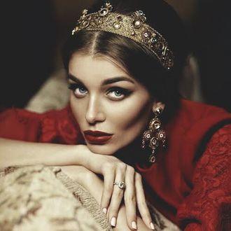 Фото Девушка в красном платье с короной на голове и серьгах в ушах