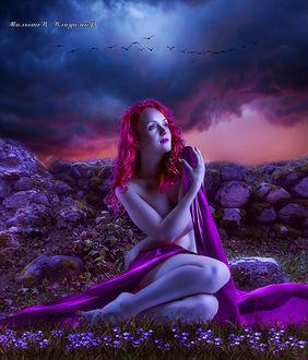 Фото Девушка в красной накидке сидит на цветах и любуется закатом