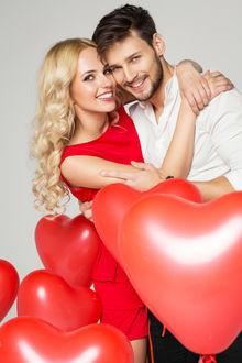 Фото Девушка обнимает парня, рядом много красных надувных шаров в виде сердец