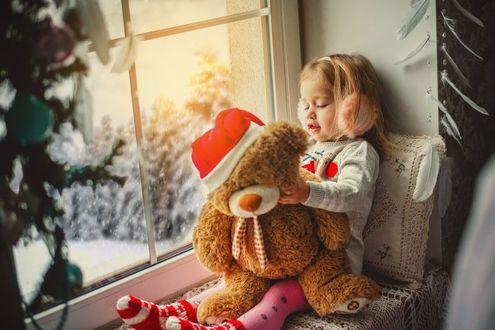 Фото Девочка с игрушечным мишкой сидит у окна