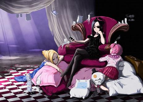 Фото Брюнетка в черном с повязкой на глазу сидит в большом кресле, рядом на подушках две девочки и игрушки
