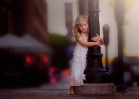 Фото Белокурая девочка стоит на городской улице, обхватив руками столб