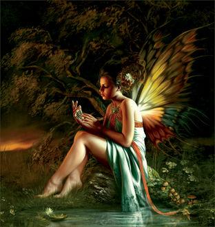 Фото Девушка-бабочка с цветами на волосах сидит на камне у лесного ручья держа в руке кулон, by Melanie Delon