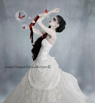 Фото Девушка с красными атласными лентами на руке и на волосах, держит на руке бабочку, рядом с ней летают бабочки в мыльных пузырях на фоне леса в тумане, by Levana Tempest