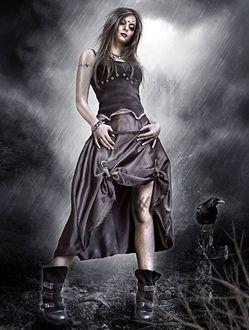 Фото Девушка с татуировкой на руке стоит под дождем у креста на могиле, на котором сидит ворон, by NatsPearlCreation