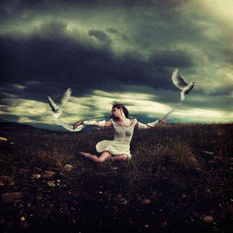 Фото Девушка сидит на траве с голубями на фоне природы