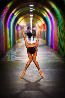 Фото Обнаженная девушка балерина, стоя на носочках в тоннеле с разноцветными стенами, наклонилась вперед, подняв руки вверх, by Dzhordan Metter