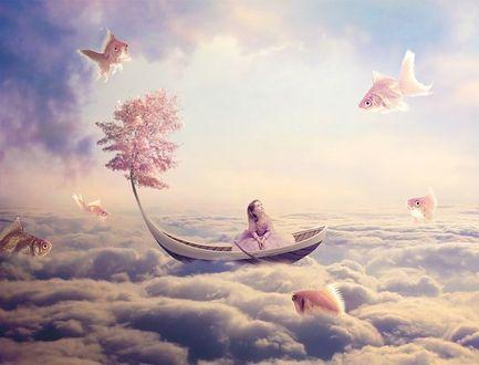 Фото Девочка, сидящая в лодке на облаках, из которой растет дерево, смотрит на летающих вокруг рыбок в небе