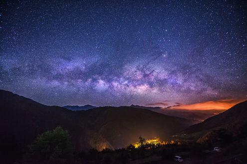 Фото Скопление звезд в ночном небе над горными хребтами