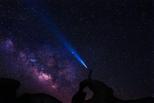 Фото Парень стоящий на выступе скалы светит фонариком в звезное ночное небо (© Margo Fly), добавлено: 25.02.2017 04:06