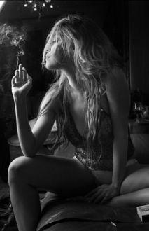 Фото Девушка с сигаретой сидит на диване