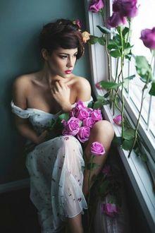 Фото Девушка с букетом роз сидит окна, на котором стоят розы