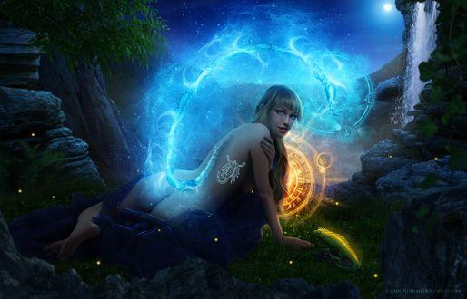 Фото Обнаженная девушка со светящейся татуировкой на спине и хвостом с неоновым свечением лежит на земле среди камней и зодиакального круга, рядом с ней ящерица