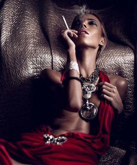 Фото Девушка в красном с украшениях на шее держит в руке сигарету, фотограф Chapala Dmitry