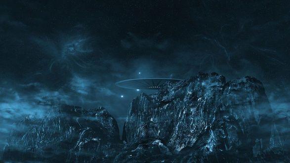 Фото Над скалами висит НЛО на фоне темного неба