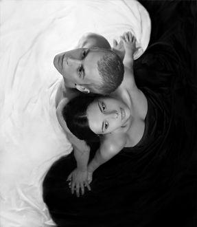 Фото Девушка и парень, взявшись за руки, сидят спиной к друг другу