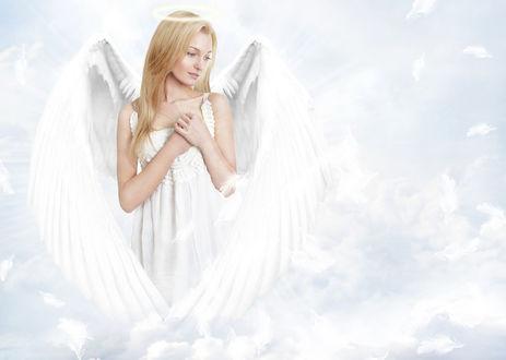 Фото Девушка - ангел белокрылый с ореолом над головой прижимает руки к груди на фоне облаков