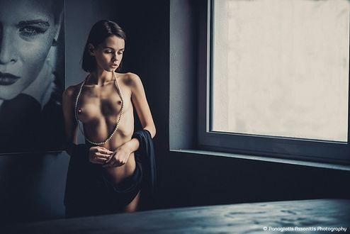 Фото Обнаженная девушка c бусами стоит у окна, by Panagiotis Assonitis