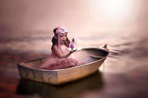 Фото Маленькая девочка, сидящая в лодке, держит девочку - мотылька на руке и удивленно смотрит на нее