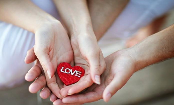 Руки девушки бережно держат сердечко с надписью Love / любовь над руками парня