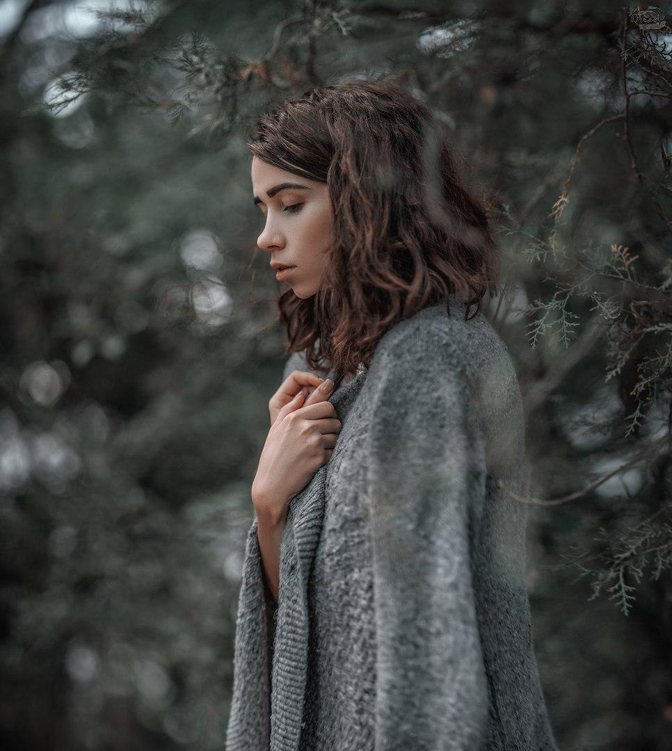 Фото Грустная девушка в вязаной кофте, стоит на размытом фоне природы, фотограф Александр Боцман