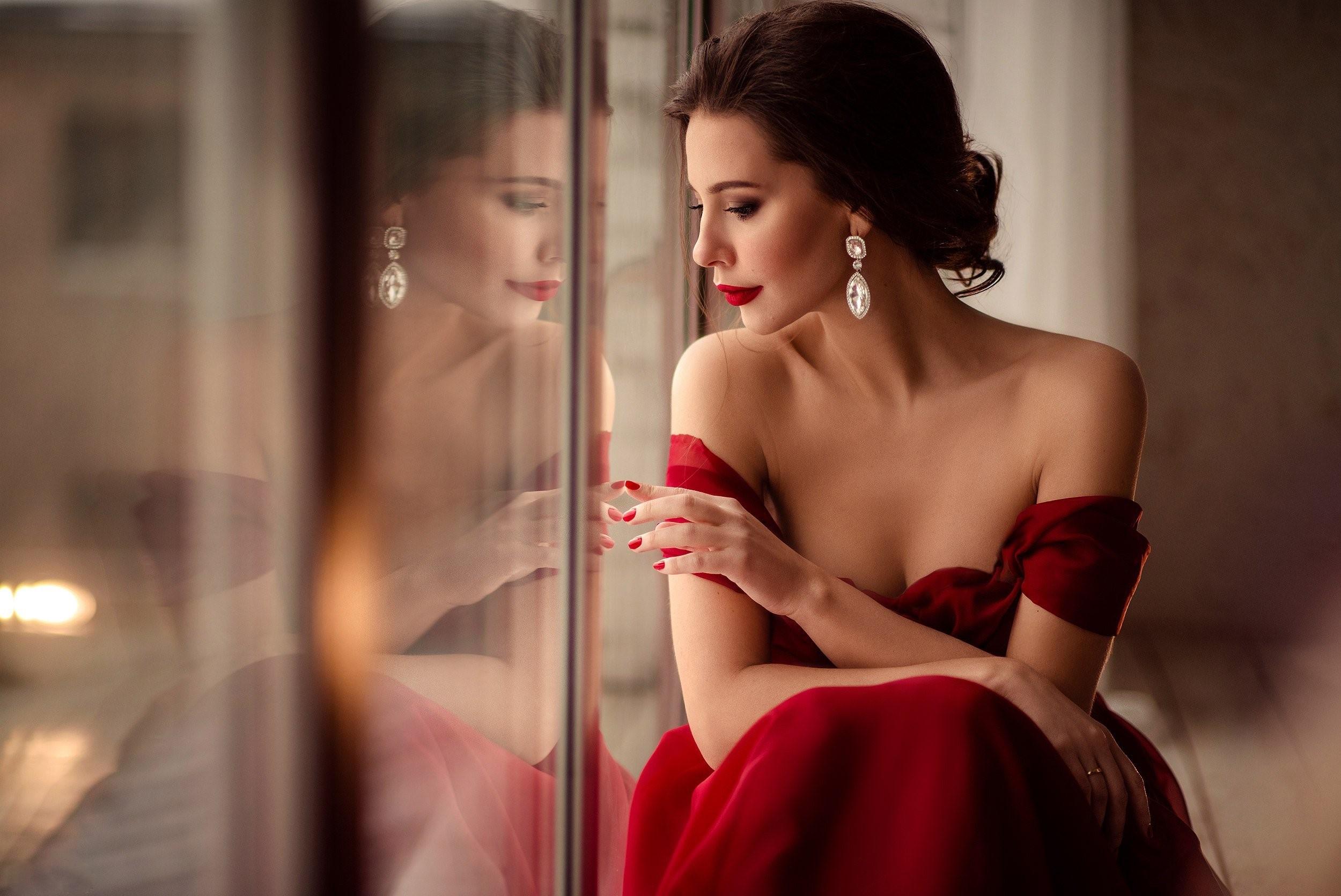Фото Девушка в красном платье с оголенными плечами сидит у окна, в котром видно ее отражение