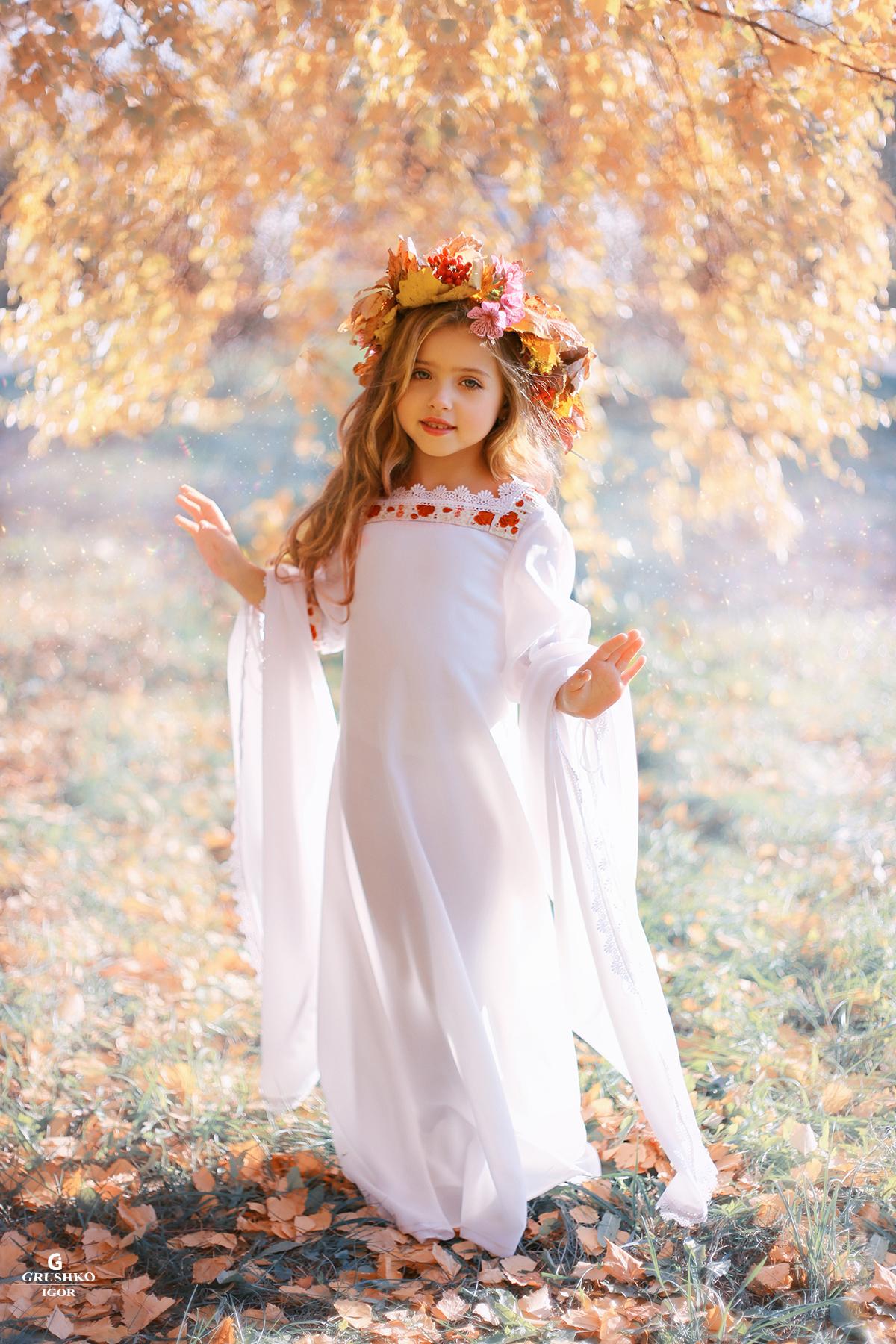 Фото Девочка в белом длинном платье с венком из цветов и листьев на голове, стоит на траве с осенними листьями, by Vayne17
