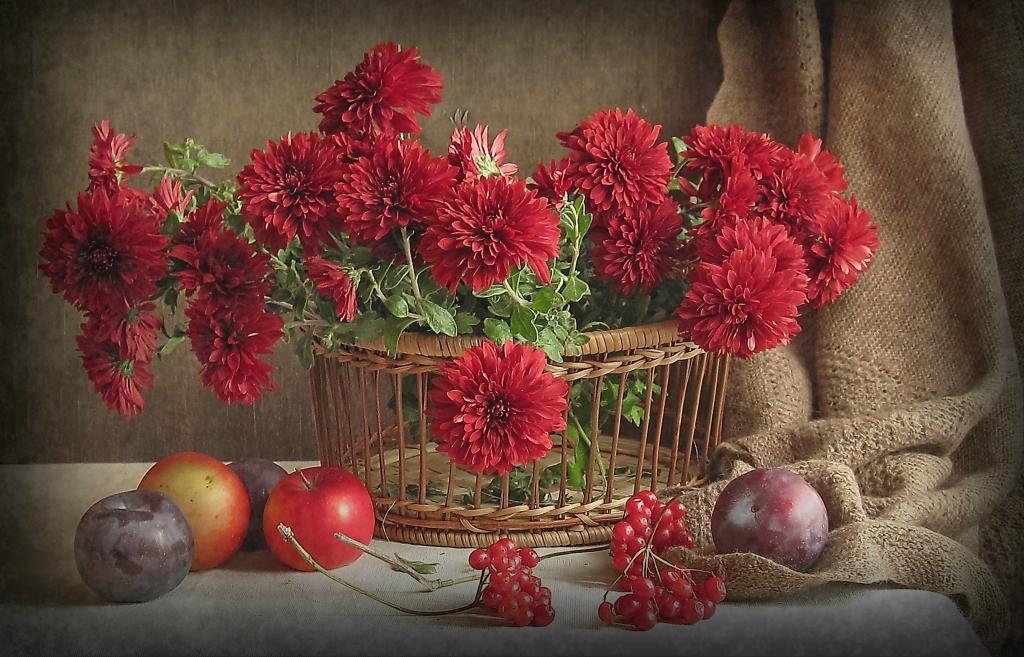 Фото Натюрморт с красными цветами в плетеннке, ягодами и фруктами