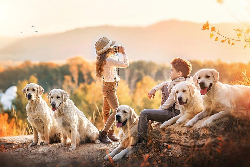 Фото Девочка с биноклем стоит за сидящими собаками, а мальчик сидит в окружении их, фотограф Ирина Недялкова