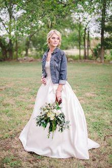 Фото Девушка в белом длинном платье, в джинсовой куртке, с букетом цветов и веточек с листьями, стоит на фоне природы, смотря в сторону