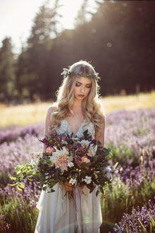 Фото Девушка в венке из луговых трав и цветов, в белом платье, с букетом цветов, стоит на размытом фоне природы, опустив голову вниз