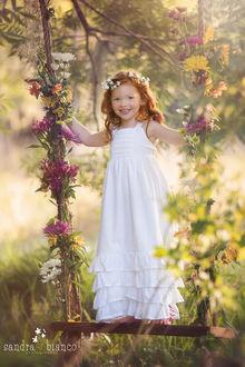 Фото Рыжеволосая улыбающаяся девочка, в белом платье, с венком на голове стоит на качели, украшенной цветами, by Sandra Bianco
