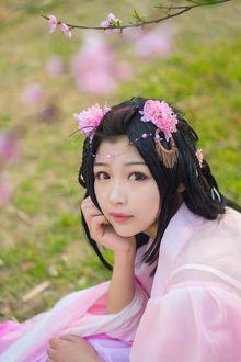 Фото Девушка в розовой одежде, с карими глазами, с украшениями и цветами на волосах, сидит на размытом летнем фоне природы под веточкой с цветами