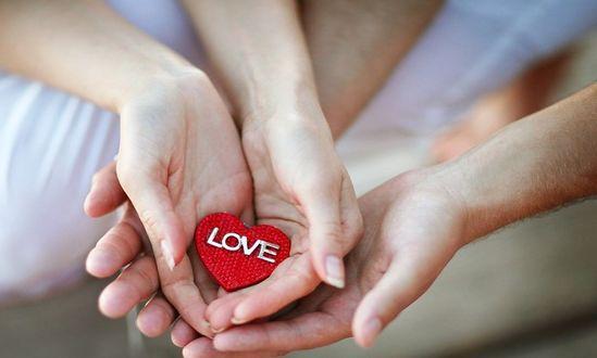 Фото Руки девушки бережно держат сердечко с надписью Love / любовь над руками парня