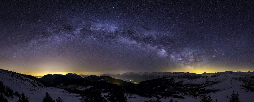 Фото Млечный путь в ночном небе над заснеженной горной долиной