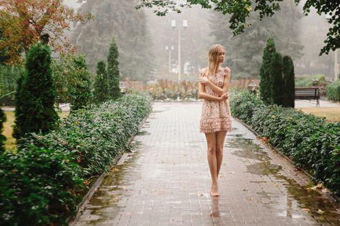 Фото Босоногая грустная девушка, в коротком платье, с закрытыми глазами, идет по вымощенной дорожке в парке, на фоне природы и фонтана, Фотограф Георгий Чернядьев