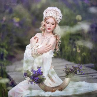 Фото Девушка с опущенyыми глазами, в головном уборе, с украшениями, в белом платье, с оголенными плечами, сидит на мостке, на фоне природы, by Margarita Kareva