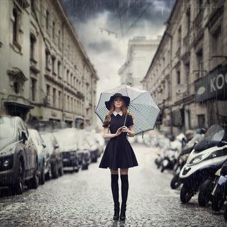 Фото Девушка в темном платье, в шляпе, с зонтом, стоит под дождем, на фоне городского переулка, by Margarita Kareva