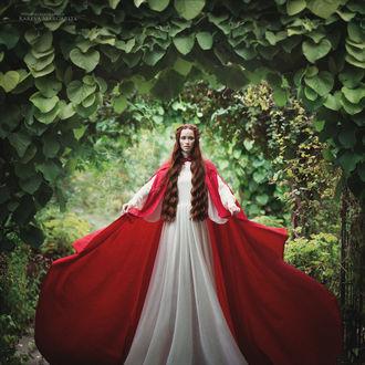 Фото Рыжеволосая девушка, в белом длинном платье, в красном длинном плаще, стоит на фоне природы, by Margarita Kareva