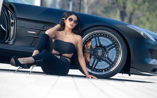 Фото Девушка в солнцезащитных очках, сидит рядом с авто