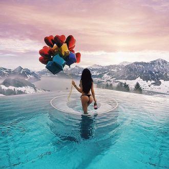 Фото Девушка в купальнике, с воздушными шарами и бутылкой шампанского в руках, стоит в воде