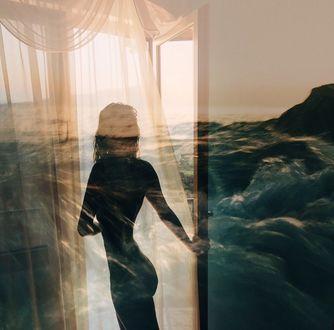 Фото Обнаженная девушка стоит у двери, на фоне моря. Фотограф Ксения Засецкая