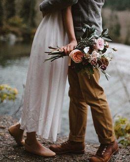 Фото Парень обнимает девушку с цветами в руке