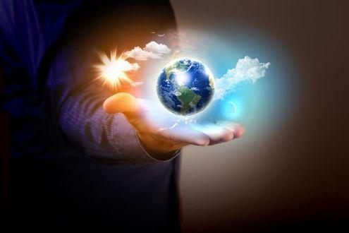 Фото Над рукой в волшебном свете парит земной шар в окружении облаков, с ним и его неразлучная спутница - Луна