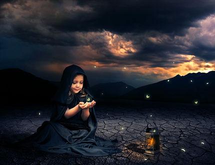 Фото На потрескавшейся земле сидит улыбающаяся девочка, над ее руками парит светящийся мотылек, рядом стоит фонарь, на фоне горного пейзажа