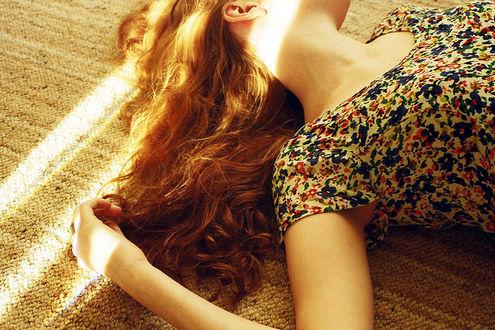 Фото Девушка лежит на полу в падающем на нее солнечном свете